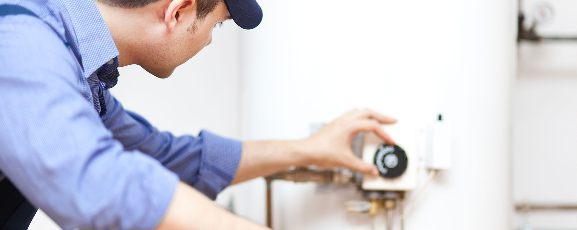 A man working on a water heater representing the water heater services by John J. Cahill servicing Chicago, IL